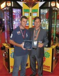Michael Peretz (left), and Dr. David Peretz holding the 2011 Brass Ring Award presented by the IAAPA Awards Committee at the 2011 IAAPA Attractions Expo.