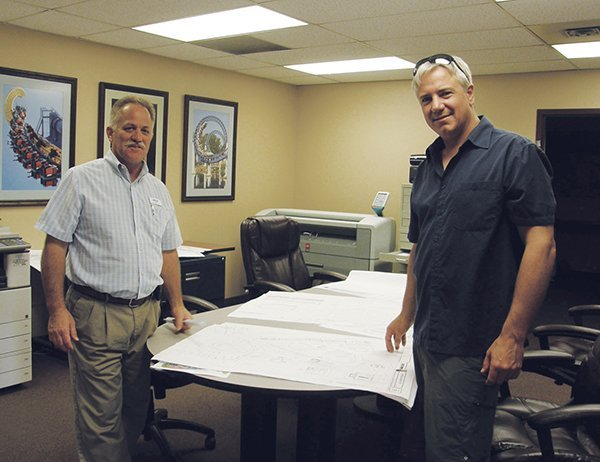Tom Suel, director of maintenance and construction at Valleyfair, (left), with Peter Loewen, owner and manager of Gould Manufacturing, taking a break to be photographed as they review drawings of the Gould ride's new location in the park.