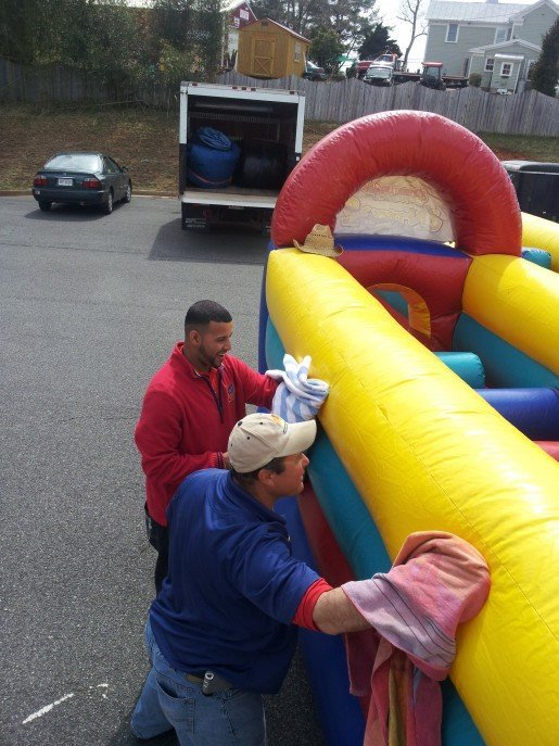 "Super Fun Inflatables staff members cleaning a unit. The owner of this Ruckersville, Va., company is interviewed in the story ""Best Bets for Successful Blowouts – Trends in Party Inflatables"" for the June 2015 issue of TAP."