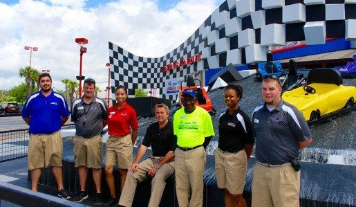 Staff members from Broadway Grand Prix are, from left to right: Ryan Dzergoski, operations manager; Bob Foltz, operations manager; Alexis Brown, admissions supervisor; David Melton, general manager; Curtis Judkins, pit crew; Jasmine Stanley, food and beverage supervisor; and Jesse Shade, admissions manager. During training, staff members receive instruction on the proper way to wear the location's uniforms.