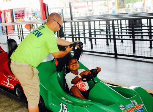 Justin Pulliam, a pit crew ride attendant, works with a restraint at Broadway Grand Prix. A Bonus Bucks incentive program is an added extra for staff members.