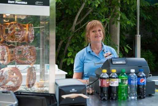 """Susan Riches, food and beverage team member, working a pretzel cart at Zoombezi Bay, a waterpark adjacent to the Columbus Zoo and Aquarium in Powell, Ohio. """"Design your menu for peak meal periods. For your busiest locations, reduce your menu to four to six key items that your team can produce quickly and consistently,"""" the waterpark's assistant director said."""