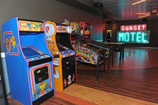 Arcade games at Bowlero Mar Vista, with a vintage neon hotel sign that enhances the center's road trip theme.