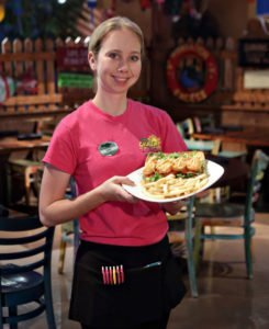 Niki White, a server at KeyLime Cove Indoor Waterpark Resort in Gurnee, Ill., photographed holding a Shrimp Po Boy that consists of hand-breaded shrimp tucked inside a hoagie roll with lettuce, tomato and house-made Keylime Mustard. The attraction has several full-service restaurants.