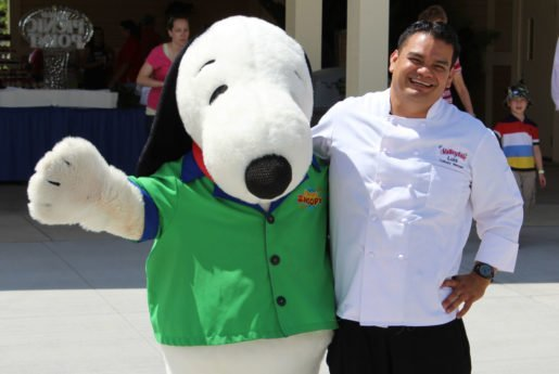 Valleyfair Executive Chef Luis Carrillo with a Snoopy character. A local brewery recently crafted a specialty brew for the park's 40th anniversary.