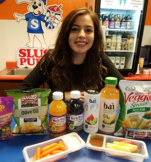 Liliana Hernandez, kitchen assistant with Rock n Roller Rink, LLC, pictured with some of the center's snack selection.