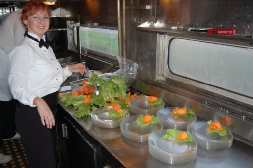 A worker at  the Lake Superior Railroad Museum & North Shore Scenic Railroad setting up plates. The location sometimes buys special items such as food trays from caterers.