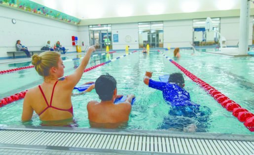 Water Safety Instructor Julia Douglas, with two swimmers, at the Troy Community Center in Troy, Mich. The facility's recreation supervisor said safe operations can depend on management's hiring of adequate personnel.