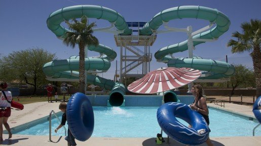 A Big Surf Waterpark ride, with guests carrying tubes in the foreground. The park's wave pool is surrounded by dozens of other attractions.