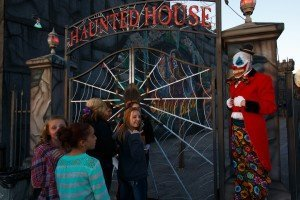 Nightmare on 13th's Stilt Clown Rolland Garret and customers photographed in front of the Spider Gate entrance to the courtyard. The haunt's circus-themed section, CarnEvil, will be expanded in 2015.