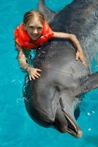 Little Smiling Girl Swimming With The Dolphin