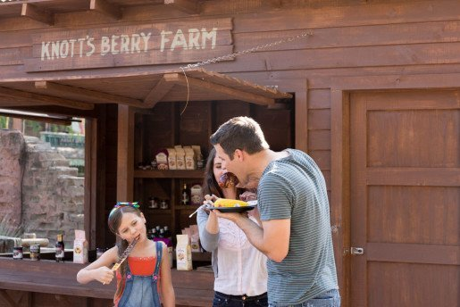 A family eating on the go at Knott's Berry Farm in Buena Park, Calif. Workers at the park's carts serve up such specialty items as smoked turkey legs and chocolate-drizzled cheesecake.