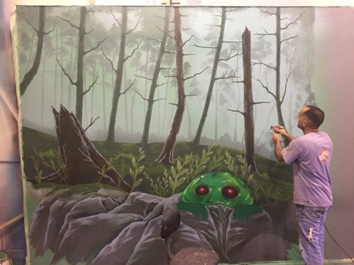A lead artist with Studio 41b paints a mural. Spare Time's new laser tag arena, which fits 24 players at a time for 15-minute sessions, aims to be a premium venue for birthday parties and team events.