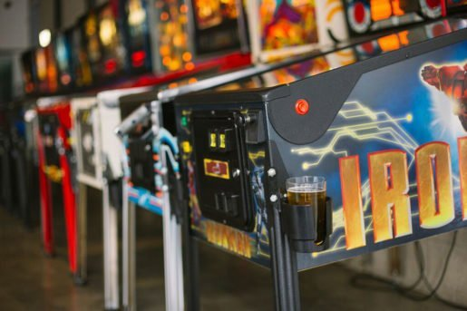 Pinball machines, one shown equipped with a beverage holder, at EightyTwo. Some guests come for the nostalgia while others are experiencing the game collection for the first time.