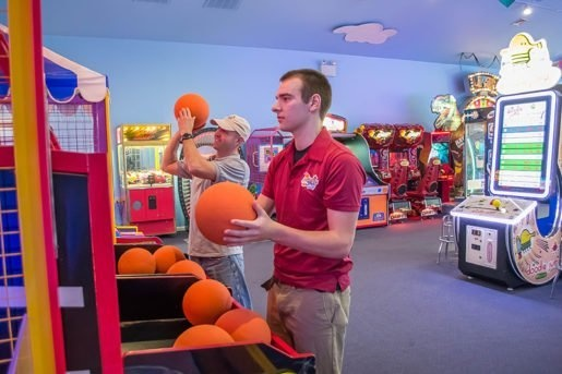 Erik Peffley, facilities manager, with Jared Landis, staff member, playing a ball shooting game at Adventure Sports. The February/March 2017 issue of TAP includes extensive arcade coverage.