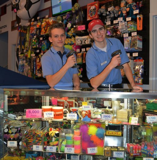If customers are working toward a goal of winning attractive prizes, the arcade will do well, according to the owner of Laser Flash. Shown at the attraction's prize center are staff members Cameron Leffler, left, and Elliott Street. The pair are holding barcode scanners used to track prize and play card values. Photo by Laura Aadson.