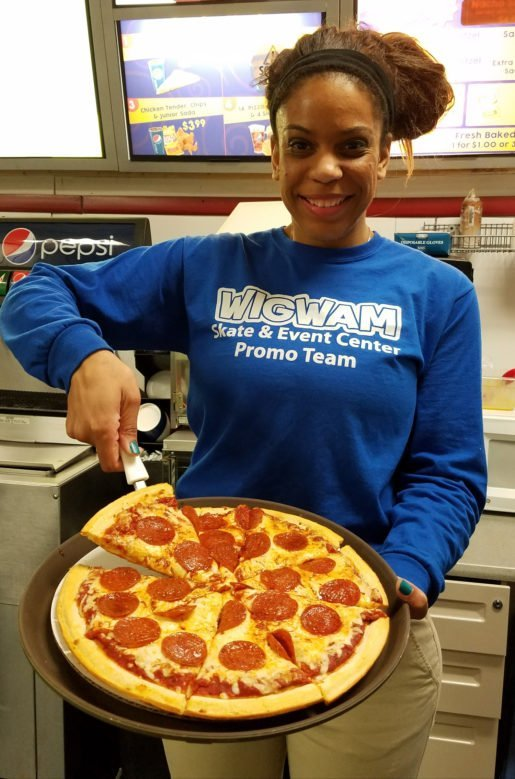 A Wigwam Skate and Event Center employee photographed with a pizza. Fresh, never frozen, grated cheese is used on the center's pies.